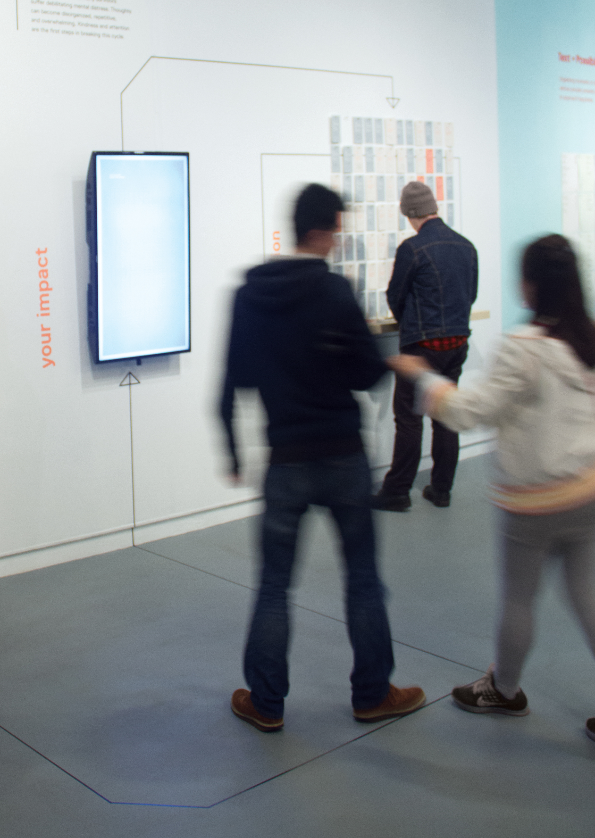 Exhibition visitors approach the interactive screen.