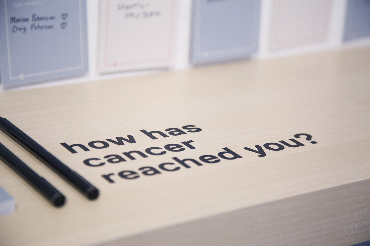 Black letters on a wooden shelf ask visitors 'how has cancer reached you?'